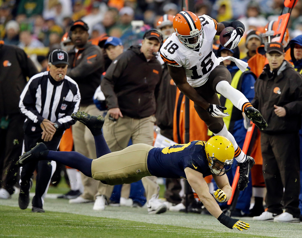 . Cleveland Browns\' Greg Little (18) leaps over Green Bay Packers\' A.J. Hawk after a catch during the second half of an NFL football game Sunday, Oct. 20, 2013, in Green Bay, Wis. (AP Photo/Tom Lynn)