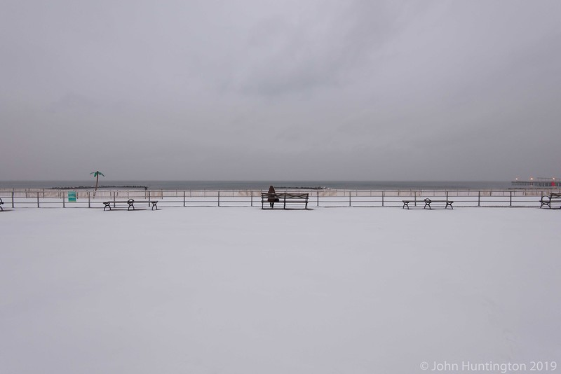 A woman sitting on a bench at Coney Island at the start of a blizzard.