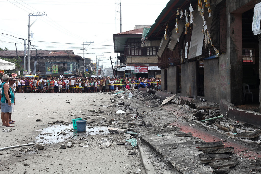 . Residents look at a collapsed portion of the fish port at Pasil in Cebu, central Philippines, Tuesday, Oct. 15, 2013.  (AP Photo/Chester Baldicantos)