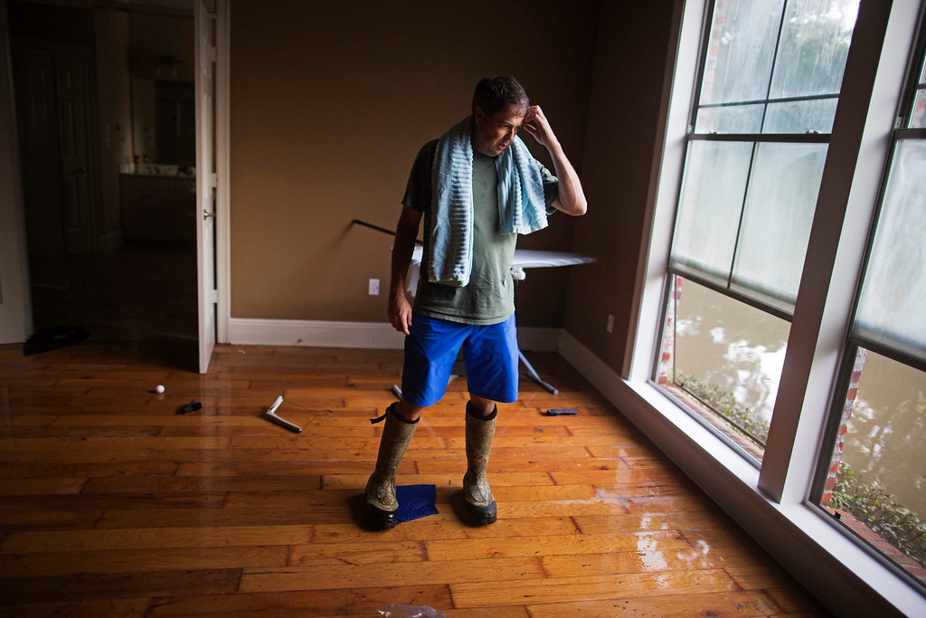 . David Key looks at water out of his master bedroom windows in his flooded home in Prairieville, La., Tuesday, Aug. 16, 2016. Key, an insurance adjuster, fled his home as the flood water was rising with his wife and three children and returned today to assess the damage. (AP Photo/Max Becherer)