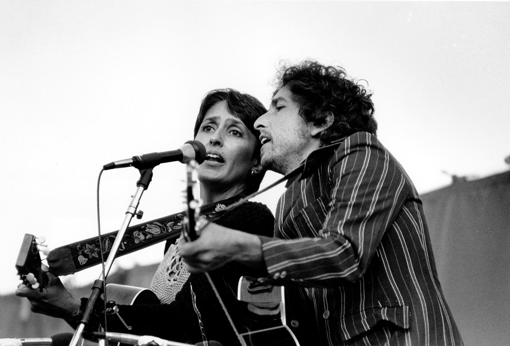 """. Folk singers Joan Baez, left, and Bob Dylan entertain over 80,000 people gathered at the Rose Bowl in Pasadena, Ca. on Sunday afternoon, June 6, 1982. The event, a nuclear disarmament rally titled \""""Peace Sunday,\"""" featured music, speeches and prayers. The rally is held just one day before the United Nations starts its special session on disarmament in New York. (AP Photo/Lennox McLendon)"""