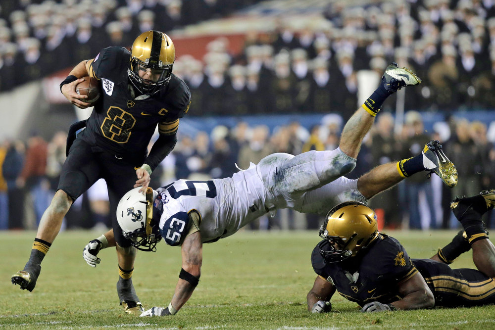 . Army\'s Trent Steelman, left, rushes past Navy\'s Cody Peterson, center, who is upended by by block from Larry Dixon, during the second half of an NCAA college football game, Saturday, Dec. 8, 2012, in Philadelphia. Navy won 17-13. (AP Photo/Matt Slocum)