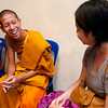 Volunteer speaks English with Buddhist monk.