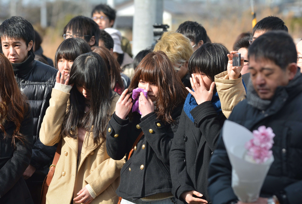 . Women (C) cry during a memorial service for tsunami victims at former Yuriage junior high school in Natori, Miyagi Prefecture on March 11, 2014 to mark the third anniversary of the quake-tsunami disaster which swept away thousands of victims, destroyed coastal communities, and sparked the nuclear emergency that forced a re-think on atomic power. The 9.0 magnitude earthquake in 2011 sent a huge wall of water into the coast of the Tohoku region, splintering whole communities, ruining swathes of prime farmland and killing nearly 19,000 people. (KAZUHIRO NOGI/AFP/Getty Images)