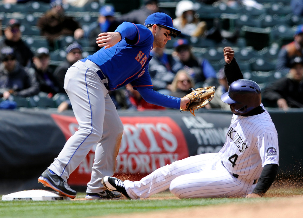 . Colorado Rockies\' Chris Nelson is forced out at third by New York Mets third baseman David Wright during the second inning of a baseball game on Thursday, April 18, 2013, in Denver. (AP Photo/Jack Dempsey)