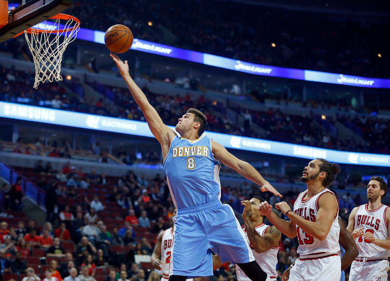 . Denver Nuggets forward Danilo Gallinari (8) goes in for a lay-up past Chicago Bulls center Joakim Noah (13) during the first half of a pre-season NBA basketball game in Chicago, on Monday Oct. 13, 2014. (AP Photo/Jeff Haynes)