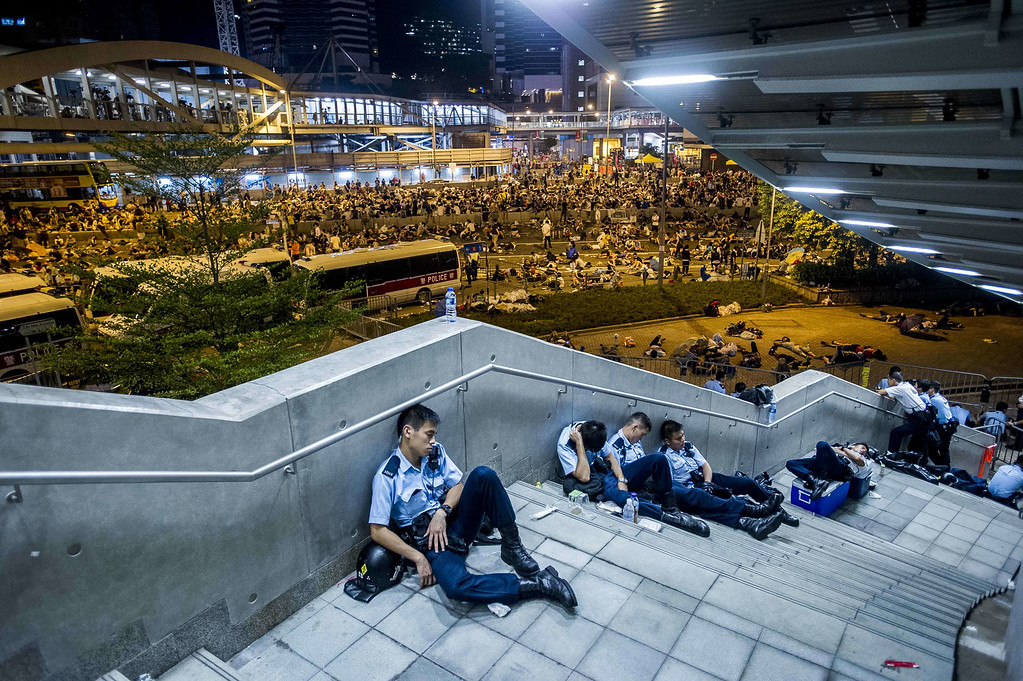 . Policemen rest following pro-democracy protests in Hong Kong on September 29, 2014.  Police fired tear gas as tens of thousands of pro-democracy demonstrators brought parts of central Hong Kong to a standstill in a dramatic escalation of protests that have gripped the semi-autonomous Chinese city for days.    AFP PHOTO / XAUME  OLLEROS/AFP/Getty Images