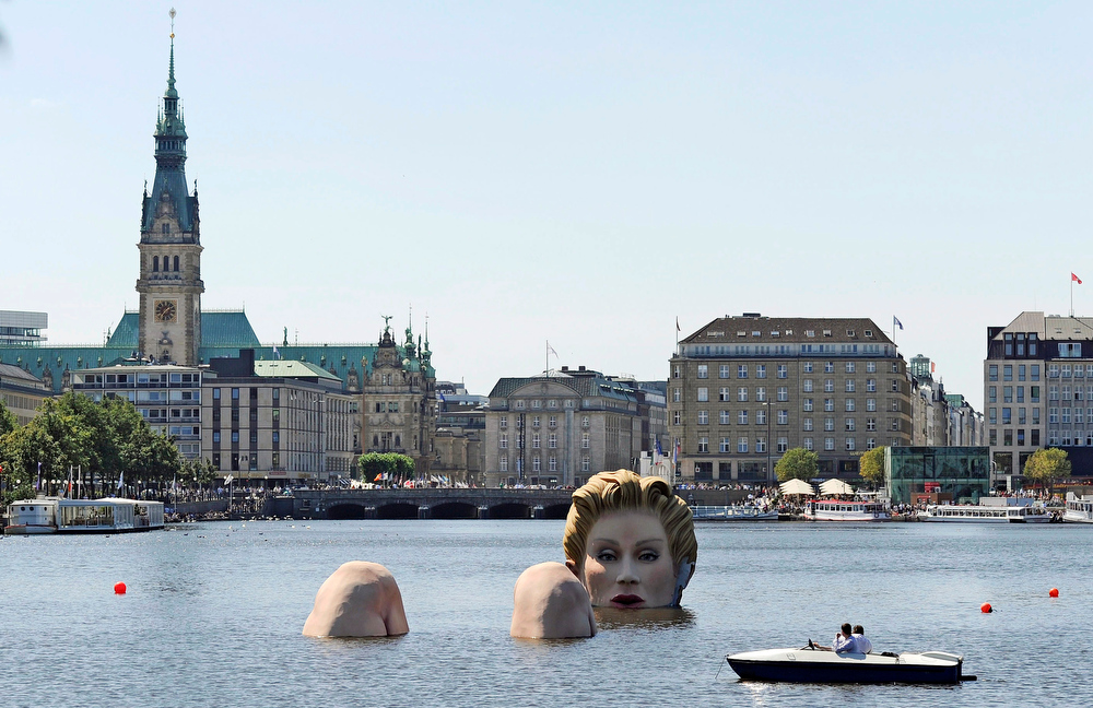 . A boat passes a sculpture of a giant mermaid designed by German artist Oliver Voss on the river Alster in Hamburg, northern Germany, Tuesday, Aug. 2, 2011. The sculpture made of styrofoam and steel will be on exhibit for ten days. (AP Photo/dapd, Axel Heimken)