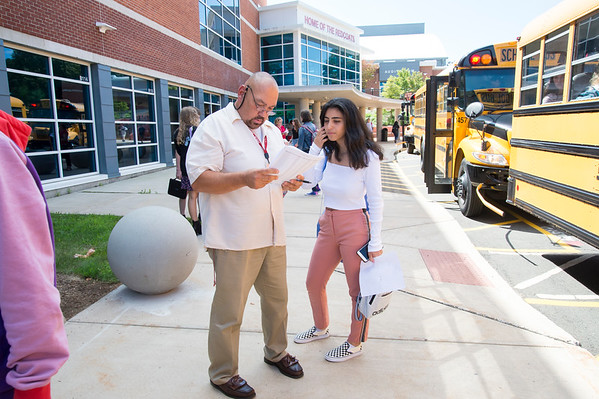 08/29/19 Wesley Bunnell | Staff Berlin High School students exit school after the first day of classes on Thursday August 29, 2019. Paul Germain helps a student find her correct bus.