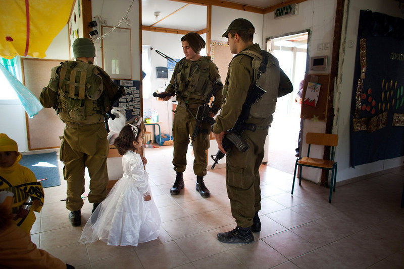 . A Jewish settler child is wearing a costume ahead of the Jewish festival of Purim as Israeli soldiers arrive to secure a Purim parade on February 22, 2013 at the settlement outpost of Havat Gilad, West Bank.  (Photo by Uriel Sinai/Getty Images)