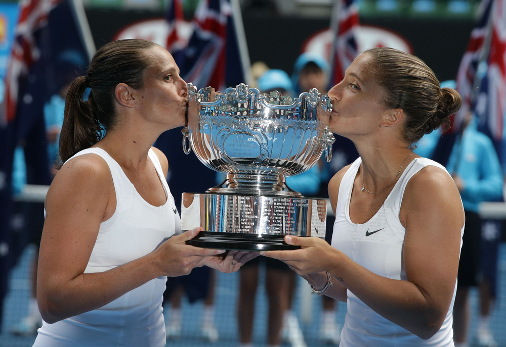 Description of . Italy's Sara Errani, right, and Roberta Vinci kiss their trophy for photographers after winning the women's doubles final against Australia's Ashleigh Barty and Casey Dellacqua at the Australian Open tennis championship in Melbourne, Australia, Friday, Jan. 25, 2013.  (AP Photo/Dita Alangkara)