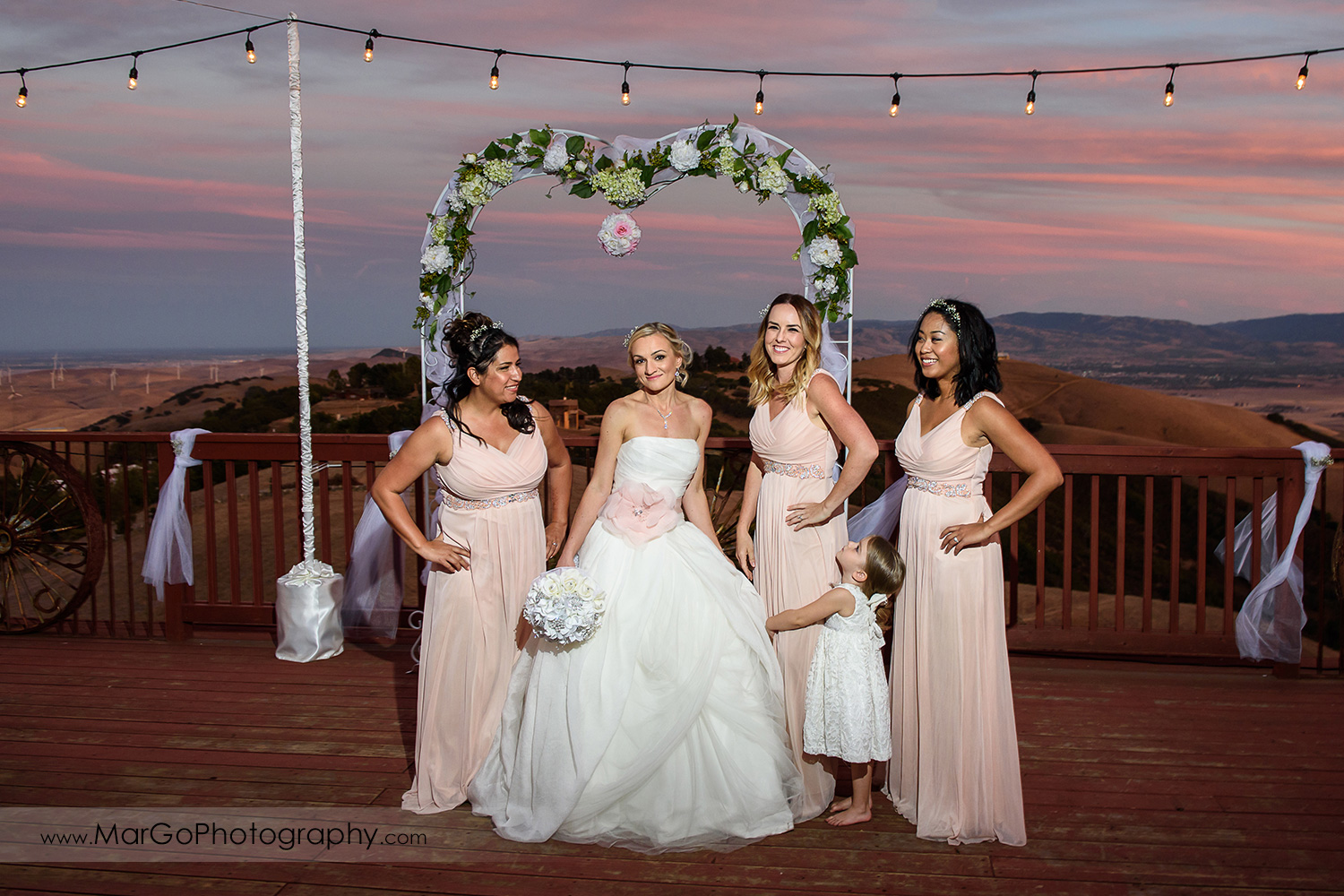bride and bridesmaids on the backyard deck with sunset hills view
