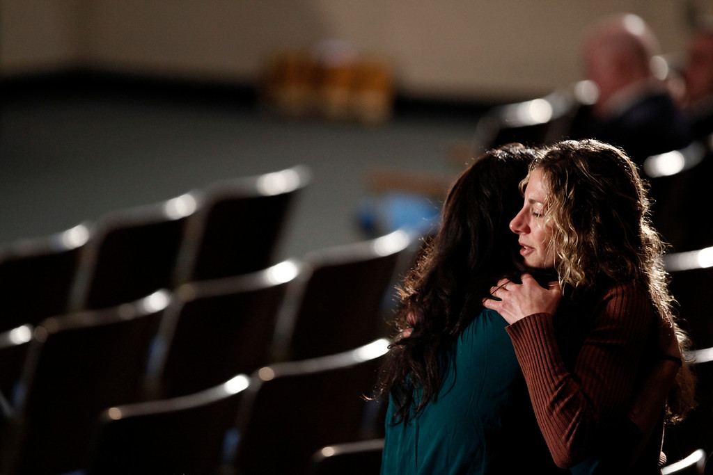 . Mourners embrace before a memorial service for victims of the shooting at Sandy Hook Elementary School in the auditorium of Newtown High School in Newtown, Conn., Dec. 16, 2012. President Barack Obama will speak at the memorial and meet privately with families and first responders. (Luke Sharrett/The New York Times)
