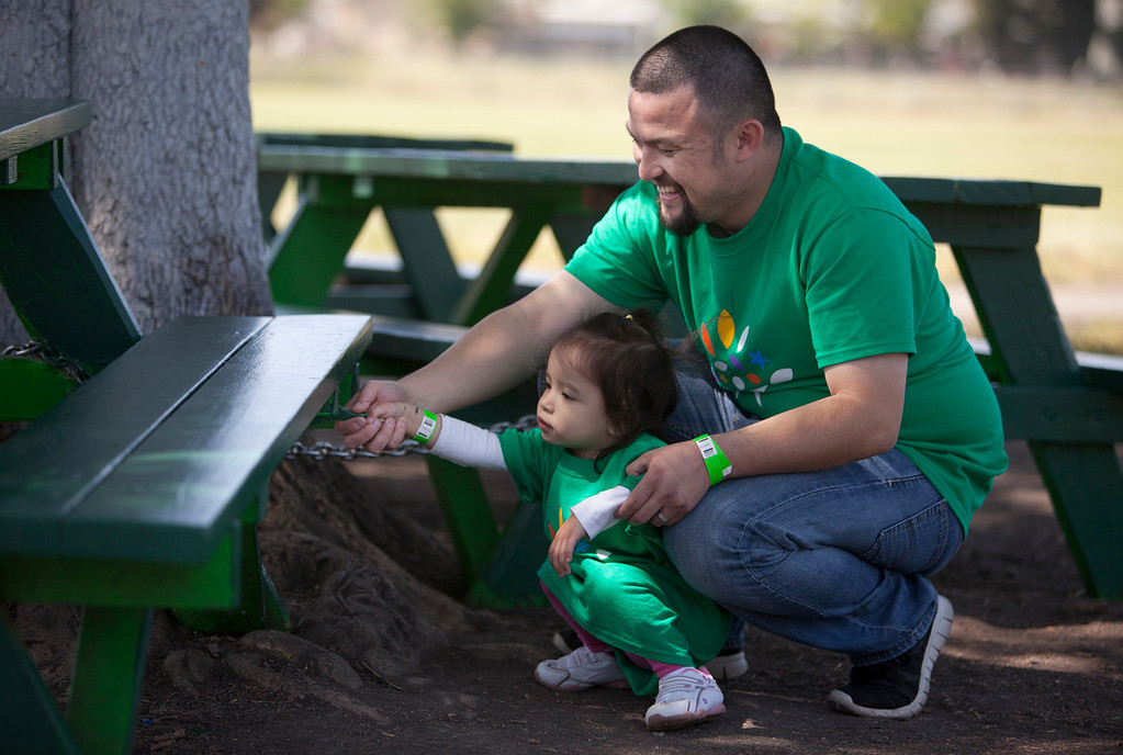 . Comcast employee Christopher Miranda of Livermore helps his daughter, Camilla, 2 1/2, paint a picnic table as local Comcast employees and their families joined with students and parents to spend the morning planting, installing benches, painting, landscaping and cleaning up the grounds at Adelante Dual Language Academy in San Jose Saturday, April 27, 2013. The volunteer effort is part of the 12th �Comcast Cares Day,� the largest single-day corporate volunteer effort in the United States that brought together more than 70,000 Comcast employees, their families and friends nationwide to help make a difference in their communities.  3,000 Comcast employees and their families did volunteer work at 16 schools affected by budget cuts in California. (Patrick Tehan/Bay Area News Group)