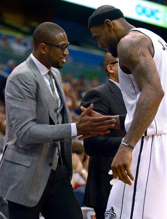 . Miami Heat forward LeBron James, right, is congratulated by teammate Dwyane Wade after James exited the game late in the second half of an NBA basketball game against the Orlando Magic in Orlando, Fla., Monday, March 25, 2013. The Heat won 108-94. (AP Photo/Phelan M. Ebenhack)