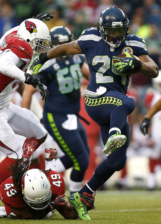 . Seattle Seahawks running back Marshawn Lynch (24) runs for a 33-yard touchdown past Arizona Cardinals strong safety Rashad Johnson (49) and inside linebacker Daryl Washington (58) during the third quarterof an NFL football game in Seattle, Sunday, Dec. 9, 2012.  (AP Photo/John Froschauer)