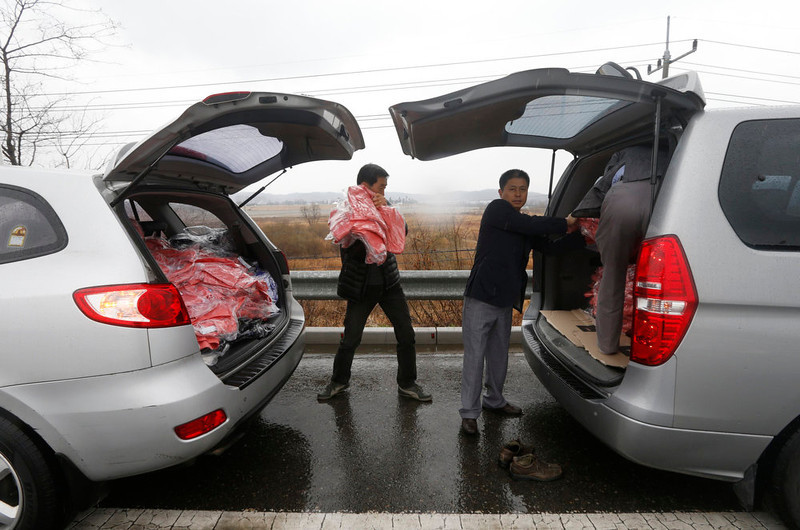 . Workers move clothes, made in North Korea\'s inter-Korean Kaesong Industrial Complex, from a van to another van on the Grand Unification Bridge, which leads to the demilitarized zone separating North Korea from South Korea, in Paju, north of Seoul April 6, 2013. The van (L) returned to South Korea from the inter-Korean Kaesong Industrial Complex. North Korea warns it could not guarantee the safety of diplomats after next Wednesday and has asked embassies to consider moving staff out of the country, European diplomats said, amid high tension on the Korean peninsula.  REUTERS/Lee Jae-Won