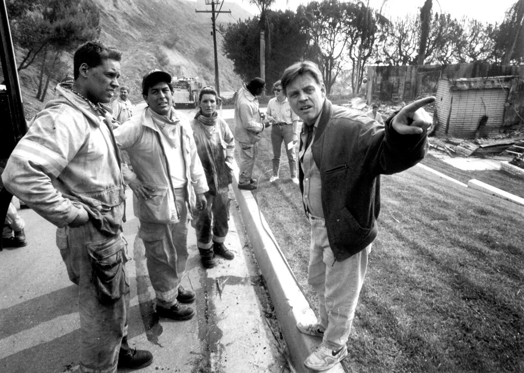 . Actor Mark Hamill talks with firefighters. His home in Big Rock survived.  (11/3/93)   Los Angeles Daily News file photo