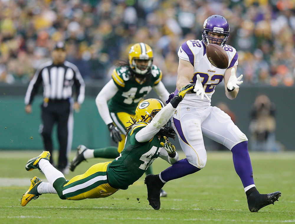 . Minnesota Vikings tight end Kyle Rudolph (82) catches a pass with Green Bay Packers free safety Morgan Burnett (42) defending during the second half of an NFL football game Sunday, Dec. 2, 2012, in Green Bay, Wis. The Packers won 23-14. (AP Photo/Morry Gash)
