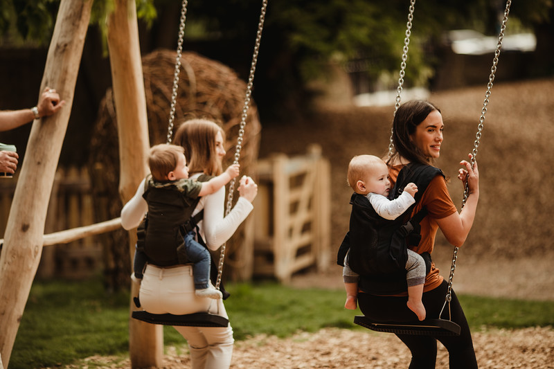 Izmi_Baby_Carrier_Olive_Lifestyle_Back_Carry_Swing_With_Friend_Pointing.jpg