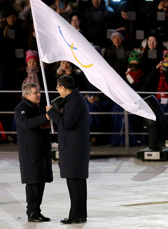 . Thomas Bach, left, president of the International Olympic Committee hands the Olympic flag to Chen Jining, mayor of Beijing, the next host city for the Winter Olympics during the closing ceremony of the 2018 Winter Olympics in Pyeongchang, South Korea, Sunday, Feb. 25, 2018. (AP Photo/Michael Probst)