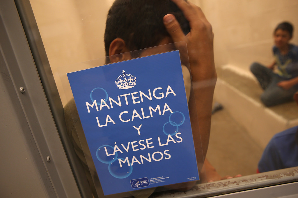 ". Junvenile immigrants wait in a holding cell at a U.S. Border Patrol processing center for immigrants detained near the U.S.-Mexico border on September 8, 2014 in McAllen, Texas. The sign, written by the U.S. Centers for Disease Control (CDC), reads ""Maintain Calm and Wash Your Hands.\""  (Photo by John Moore/Getty Images)"