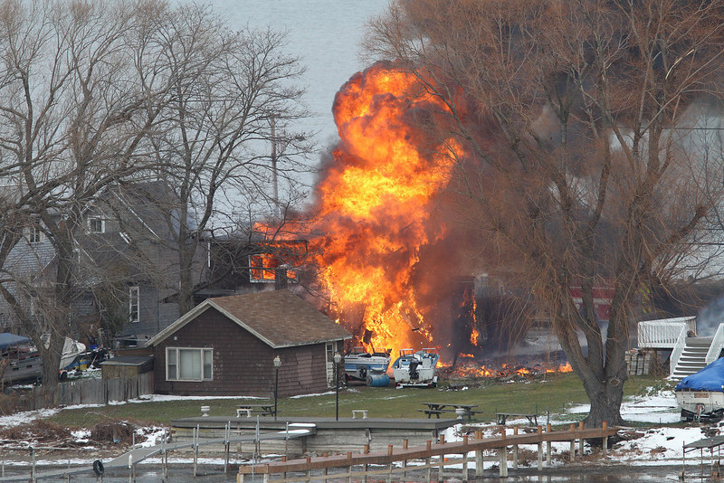 . A house burns Monday, Dec. 24, 2012 in Webster, New York. A former convict set a house and car ablaze in his lakeside New York state neighborhood to lure firefighters then opened fire on them, killing two and engaging police in a shootout before killing himself while several homes burned. Authorities used an armored vehicle to evacuate the area. (AP Photo/Democrat & Chronicle, Jamie Germano)