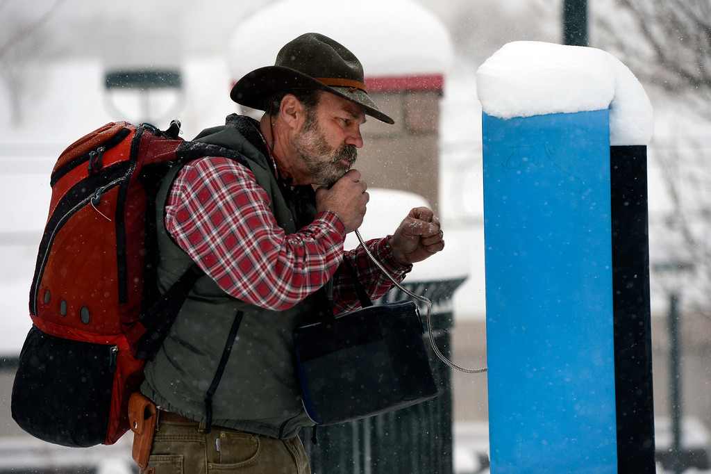 . LITTLETON, CO. - MARCH 23: (l-r) Scott Kool, of Sioux, IA, uses a pay phone to call his sister as he arrives at the  RTD station in downtown Littleton, CO March 23, 2013. The Saturday forecast calls for snow accumulation of 9 to 12 inches with highs in the lower to mid 20s. (Photo By Craig F. Walker/The Denver Post)