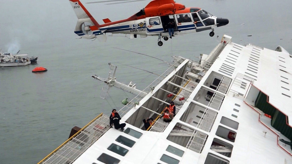 . This photo taken at sea some 20 kilometers off the island of Byungpoong in Jindo on April 16, 2014 shows South Korea Coast Guard members in helicopters trying to rescue some of the 477 passengers and crew aboard a South Korean ferry that capsized on its way to Jeju island from Incheon. South Korean officials said as many as 295 people were still unaccounted for after a ferry carrying 477 passengers and crew capsized off the south coast on April 16.      AFP PHOTO/YONHAPYONHAP/AFP/Getty Images