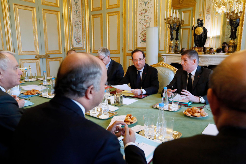 Description of . France's President Francois Hollande presides over a meeting on the Malian situation at the Elysee Palace in Paris, January 14, 2013. France's military Chief of Staff Benoit Puga is seated at right and France's Foreign Minister Laurent Fabius is seen in the foreground.  REUTERS/Kenzo Tribouillard/Pool