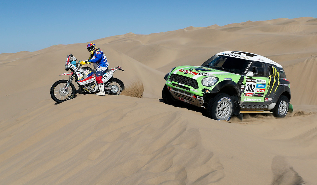 . Stephane Peterhanzel and Jean Paul Cottret, both of France, right, overtakes Yamaha rider Gustavo Querales Malave of Venezuela, left, during the 4nd stage of the 2013 Dakar Rally from Nazca to Arequipa, Peru, Tuesday, Jan. 8, 2013. The race finishes in Santiago, Chile, on Jan. 20. (AP Photo/Victor R. Caivano)