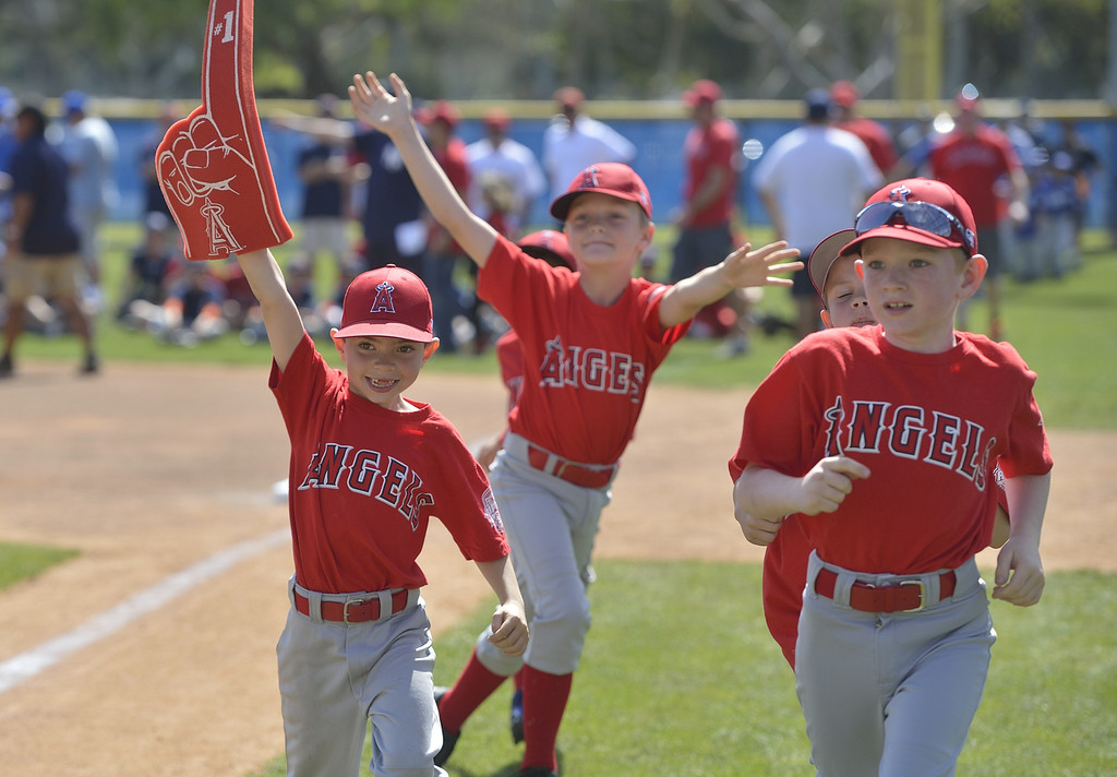 . LONG BEACH, CALIF. USA -- Angels player Joshua Hindman, 6, left, carries a big foam finger as he joins his teammates running on the field as their team is announced during opening ceremonies for The Los Altos Youth Baseball and Softball league at El Dorado Park in Long Beach, Calif. on March 2, 2013.  Photo by Jeff Gritchen / Los Angeles Newspaper Group
