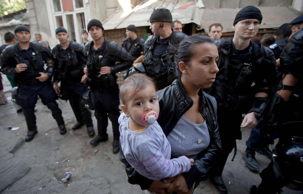 . A Roma woman holds a child as riot policemen stand by whilst more than 100 people are evicted from the homes they lived in, in Bucharest, Romania, Monday, Sept. 15, 2014. (AP Photo/Vadim Ghirda)