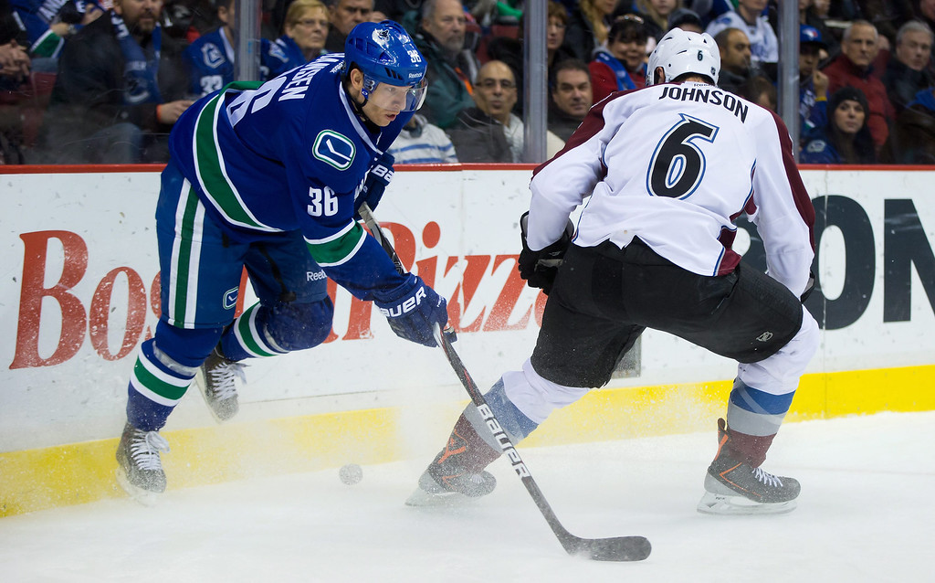 . Vancouver Canucks\' Jannik Hansen, left, of Denmark, side-steps a check by Colorado Avalanche\'s Erik Johnson during the first period of an NHL hockey game in Vancouver, British Columbia on Sunday, Dec. 8, 2013. (AP Photo/The Canadian Press, Darryl Dyck)