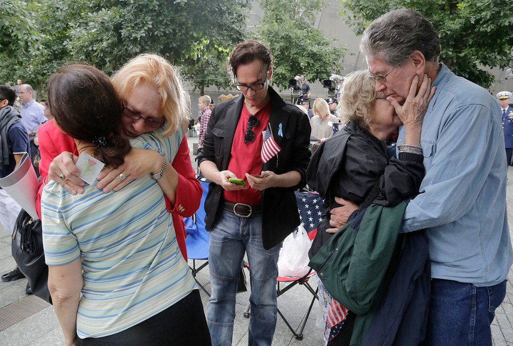 . Friends and family of Carol Ann La Plante embrace as her name is read aloud during memorial observances held at the site of the World Trade Center in New York, Thursday, Sept. 11, 2014. La Plante worked for Marsh & McLennan on the 97th floor of tower 1 and died in the attacks of Sept. 11, 2001. From left to right are: Irene Venditti, Jeanne Kavinski, Mark Trider, Marilyn Matthews and Glenn Sorensen. (AP Photo/Mark Lennihan, Pool)