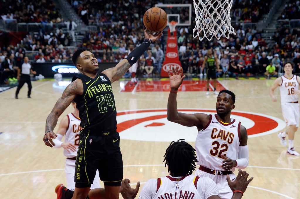 . Atlanta Hawks guard Kent Bazemore (24) goes up for a shot against Cleveland Cavaliers\' Jeff Green (32) and John Holland (10) during the second half of an NBA basketball game Friday, Feb. 9, 2018, in Atlanta. Cleveland won 123-107. (AP Photo/John Bazemore)