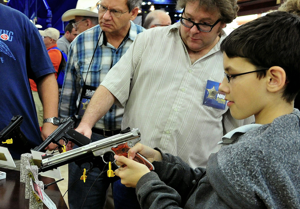 . A youngster handles a .22 handgun as his father alooks on t the NRA (National Rifle Association) Convention on May 4, 2013 in Houston, Texas.  KAREN BLEIER/AFP/Getty Images
