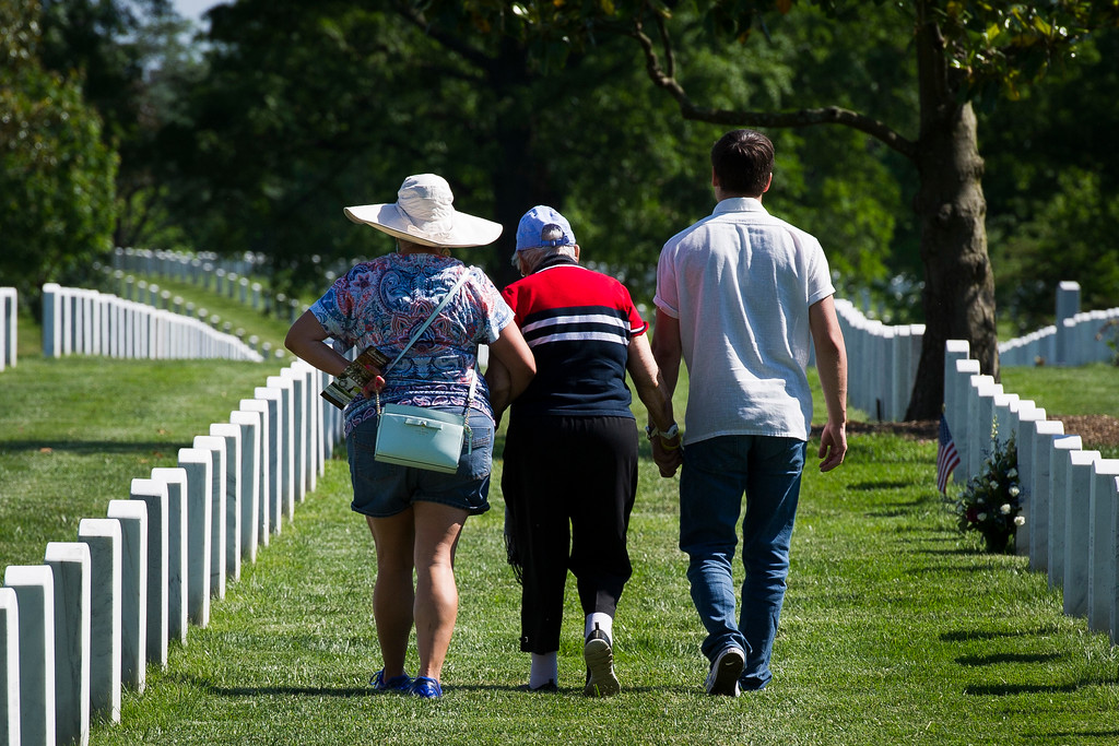 . A family holds hands as they visit Section 60 while members of the Army 3d U.S. Infantry Regiment, The Old Guard, honor the nation\'s fallen military heroes during its annual Flags In ceremony at Arlington National Cemetery, Thursday, May 24, 2018, in Arlington, Va. (AP Photo/Cliff Owen)
