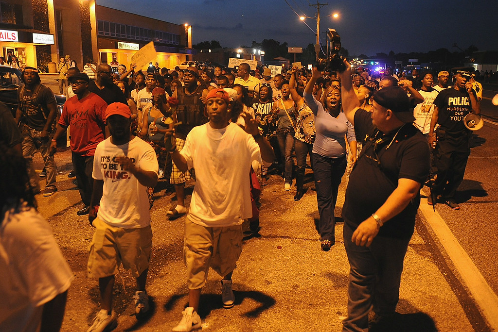 . Demonstrators march during a protest on West Florissant Avenue in Ferguson, Missouri on August 18, 2014. Police fired tear gas in another night of unrest in a Missouri town where a white police officer shot and killed an unarmed black teenager, just hours after President Barack Obama called for calm. Michael B. Thomas/AFP/Getty Images