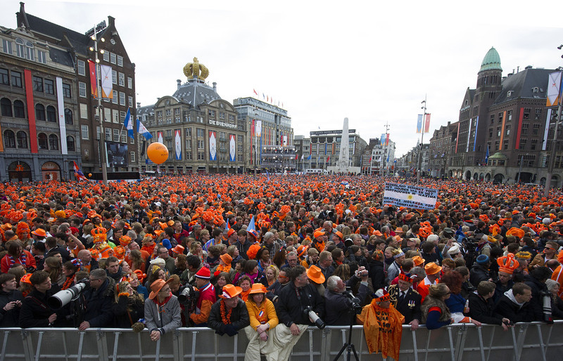 . Members of the public gather in Dam Square in front of the Royal Palace in central Amsterdam as they wait for members of the royal family to appear as Queen Beatrix abdicates and hands the throne to her son Prince Willem-Alexander on April 30, 2013.  CARL COURT/AFP/Getty Images