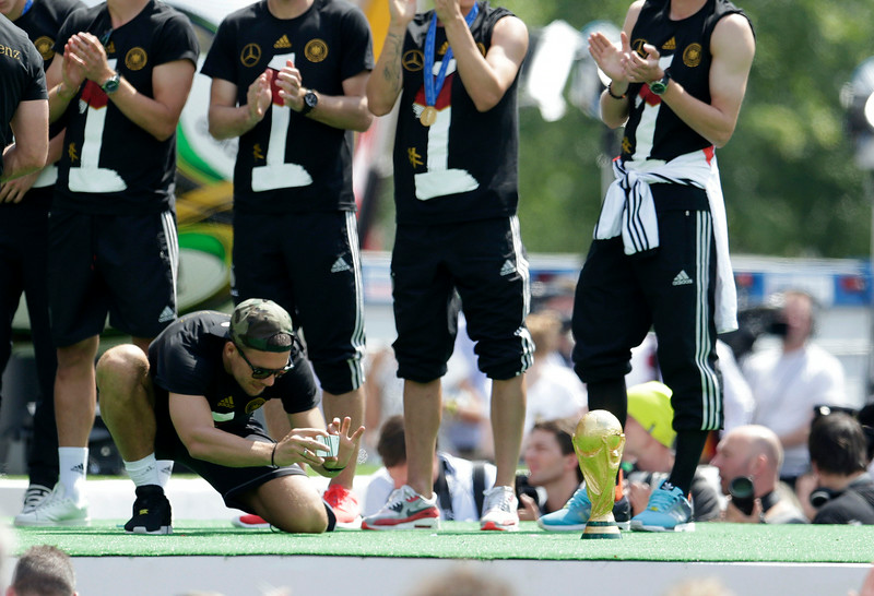 . Lukas Podolski photographs the trophy during a fan party at the Brandenburg gate after the arrival of the German national soccer team in Berlin Tuesday, July 15, 2014. Germany beat Argentina 1-0 on Sunday to win its fourth World Cup title.  (AP Photo/Petr David Josek)