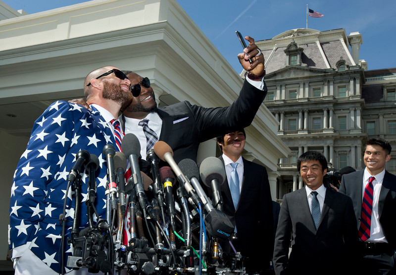 """. Boston Red Sox designate hitter David \""""Big Papi\"""" Ortiz, second from left, takes a selfie with teammate Johnny Gomes, outside White House in Washington, Tuesday, April 1, 2014, following a ceremony where President Barack Obama honored the 2013 World Series baseball champion Boston Red Sox.  (AP Photo/Manuel Balce Ceneta)"""