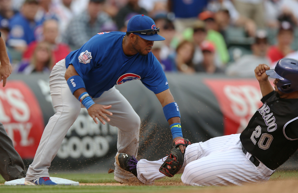 . Chicago Cubs third baseman Luis Valbuena, left, tags out Colorado Rockies\' Wilin Rosario at third base as Rosario tried to advance on a ground ball hit by DJ LeMahieu in the fifth inning of the Cubs\' 6-2 victory in a baseball game in Denver on Thursday, Aug. 7, 2014. (AP Photo/David Zalubowski)