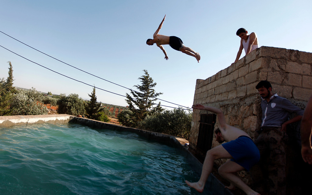 . FILE - Free Syrian Army fighters swim in a pool on the outskirts of Aleppo, Syria, Tuesday, June 12, 2012. (AP Photo/File)
