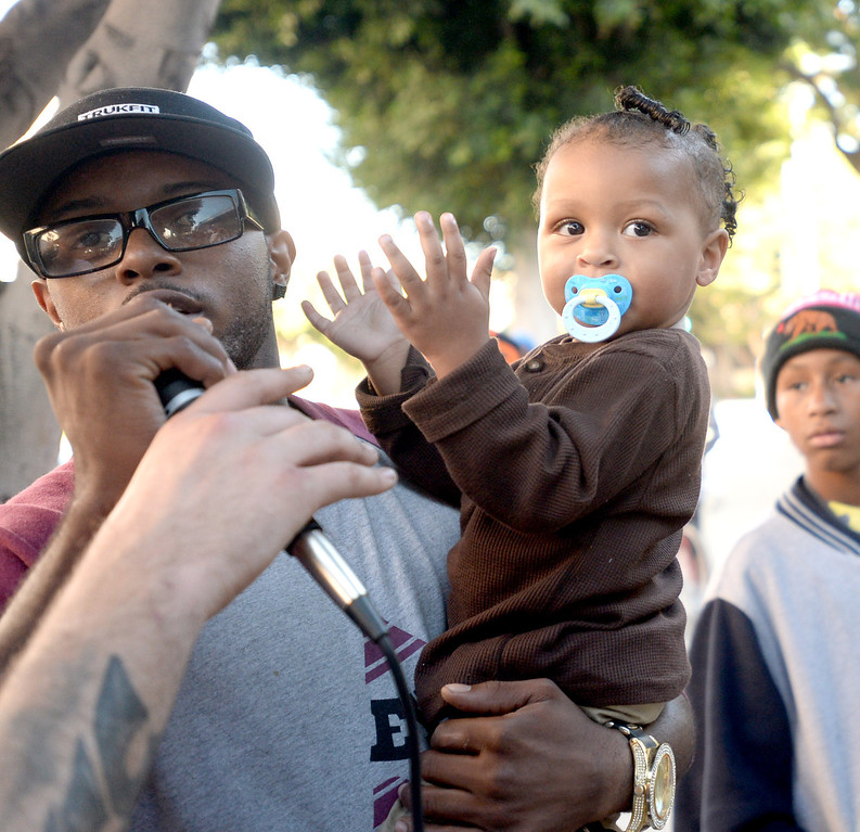 . Trevor Woods Jr., 25, left, and Nye woods,1, son of Tyler Woods, who was shot by the Long Beach Police Department on Nov. 19, protest his shooting death at the rally outside the department headquarters in Long Beach on Sunday, November 24, 2013. (Photo by Sean Hiller/ Daily Breeze).