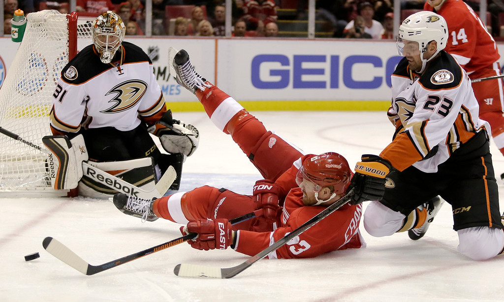 . Detroit Red Wings\' Johan Franzen (93), of Sweden, tries to get a shot off against Anaheim Ducks\' Frederik Andersen (31), of Denmark after being knocked down by Anaheim Ducks\' Francois Beauchemin (23) during the second period of an NHL hockey games Saturday, Oct. 11, 2014, in Detroit. (AP Photo/Duane Burleson)