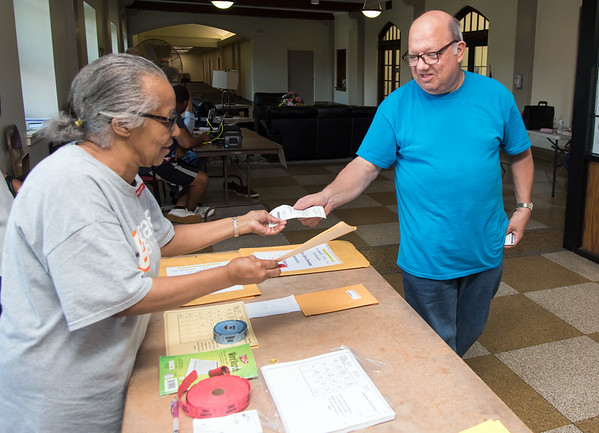 08/14/18 Wesley Bunnell | Staff William Eltman receives his official voting ballot from Ballot Clerk Margaret Shorter at voting district 5-1 at the School Apartments on Bassett St on Tuesday afternoon.
