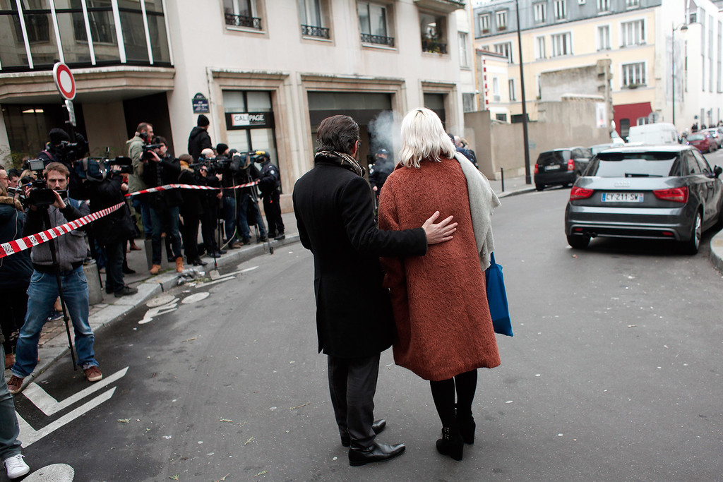 . People stand outside the French satirical newspaper Charlie Hebdo\'s office after a shooting, in Paris, Wednesday, Jan. 7, 2015. Masked gunmen stormed the offices of a French satirical newspaper Wednesday, killing at least 11 people before escaping, police and a witness said. The weekly has previously drawn condemnation from Muslims. (AP Photo/Thibault Camus)