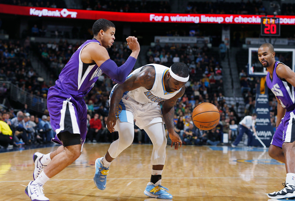 . Denver Nuggets guard Ty Lawson, center, loses control of the ball while trying to drive for a shot between Sacramento Kings guards Ray McCallum, left, and Ramon Sessions in the third quarter of the Kings\' 110-105 victory in an NBA basketball game in Denver on Monday, Nov. 3, 2014. (AP Photo/David Zalubowski)