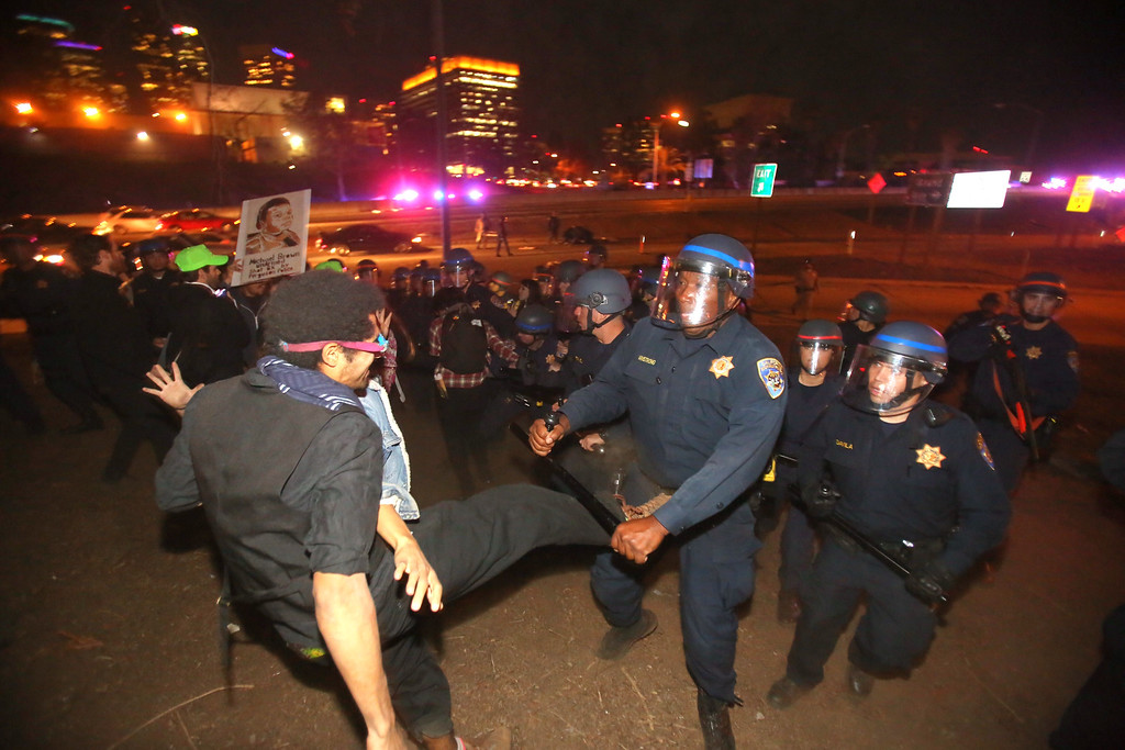 . Police officers force demonstrators to leave the Hollywood Freeway during a protest November 25, 2014 in Los Angeles, California, one day after a grand jury decision not to prosecute a white police officer for the killing of an unarmed black teen in Ferguson, Missouri.    AFP PHOTO / Ringo  CHIU/AFP/Getty Images